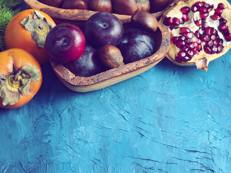 morado: Persimmons, plums, chestnuts and pomegranate on blue paper textured background with copy space. Winter still life Foto de archivo
