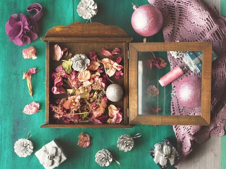 flores secas: Christmas still life with christmas tree decorations and dried flowers on dark green wooden background