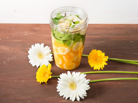 cocktail mixer: Mixer glass with fruit and vegetables for a smoothie (banana, orange juice, pear, ginger and celery) with spring color flowers around on brown wooden table