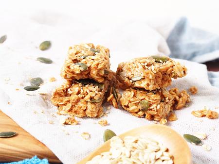 Oatmeal energy bars with oats, pumpkin seeds, peanut butter, agave syrup, sesame and sunflower seeds, closeup