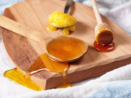 trencher: Assortment of three types of honey on wooden board, rustic background