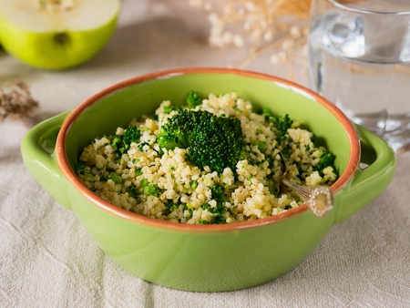 Millet porridge with broccoli in a green bowl on beige table cloth