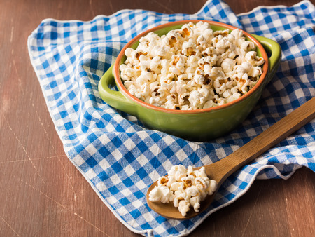 home cooked: Cooked home made popcorn in a bowl on kitchen napkin on wooden table Stock Photo