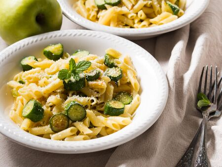 grated parmesan cheese: Pennette pasta with zucchini, fresh mint and grated parmesan cheese on beige table cloth