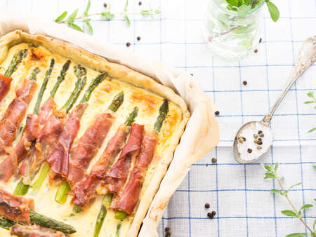 vegetable tin: Savory pie with asparagus, prosciutto, marjoram and egg and cream mixture in a baking tin with parchment on checkered table cloth