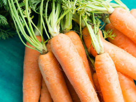 paddock: Bunch of fresh paddock carrots on green wooden background Stock Photo