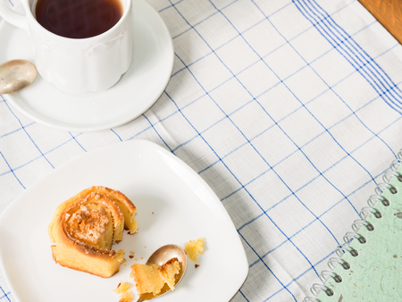 corn flour: Breakfast set with mixed wheat and corn flour roll buns and black tea on white checkered table cloth with a closed note book and copy space