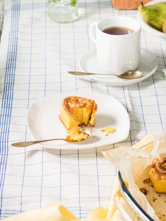 corn flour: Breakfast set with mixed wheat and corn flour roll buns and black tea on white checkered table cloth, vertical image