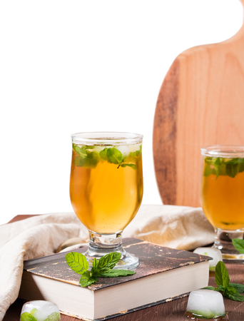 Cold tea cocktail with mint leaves and ice cubes on dark wooden table. Vetical image, partly isolated on white Stock Photo