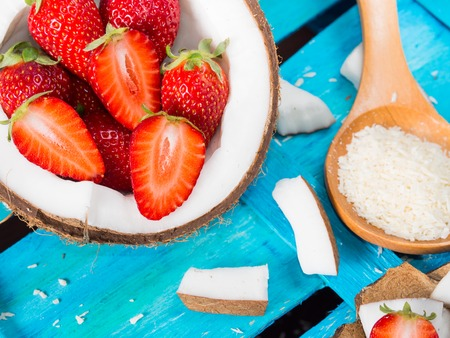 shredded coconut: Half coconut with strawberries and wedges of coconut and shredded coconut on bright blue wooden background Stock Photo