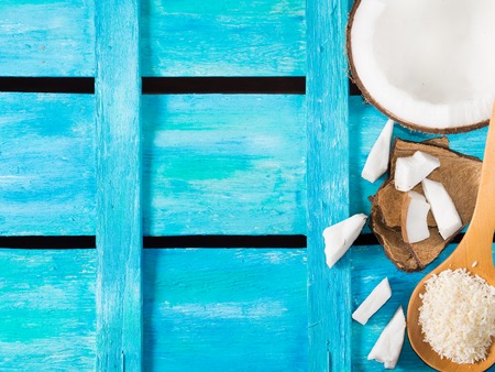 shredded coconut: Half coconut with wedges of coconut and shredded coconut on bright blue wooden background, copy space. top view
