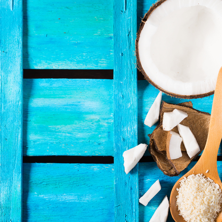 shredded coconut: Half coconut with wedges of coconut and shredded coconut on bright blue wooden background, square image