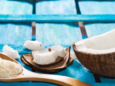shredded coconut: Half coconut with wedges of coconut and shredded coconut on bright blue wooden background