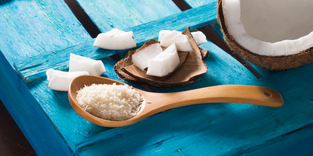 shredded coconut: Half coconut with wedges of coconut and shredded coconut on bright blue wooden background, banner image