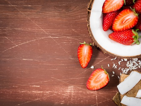 shredded coconut: Half coconut with strawberries and wedges of coconut and shredded coconut on dark wooden background