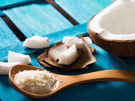 angle view: Half coconut with wedges of coconut and shredded coconut on bright blue wooden background. Angle view, copy space