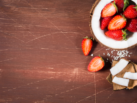 shredded coconut: Half coconut with strawberries and wedges of coconut and shredded coconut on dark wooden background. Copy space