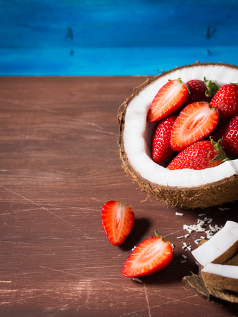 shredded coconut: Half coconut with strawberries and shredded coconut on bright blue and brown rustic wooden background. Copy space. Vertical shot Stock Photo