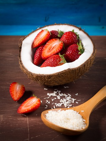 shredded coconut: Half coconut with strawberries and shredded coconut on bright blue and brown rustic wooden background Stock Photo