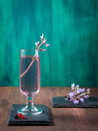 lillac: Stemmed glass with violet drink with purple flower on dark green and brown wooden background. Copy space