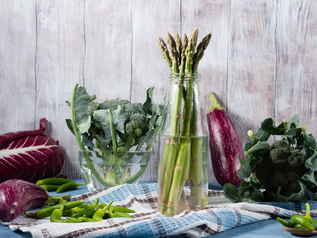 chilly: Organic green and purple vegetables on wooden background - asparagus, broccoli, eggplant, chilly peppers on napkin on wooden textured background. Copy space