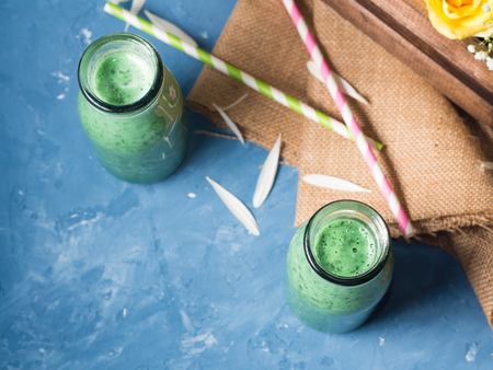 flatly: Green smoothie with banana, soy milk and basil leaves in glass bottles on bright blue background with flowers. Top view