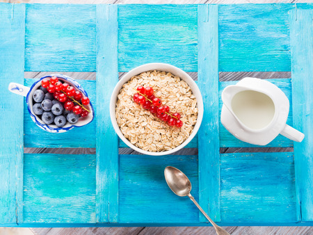 flatly: Bowl with oatmeal flakes with red currants for healthy breakfast on bright blue wooden background. Copy space