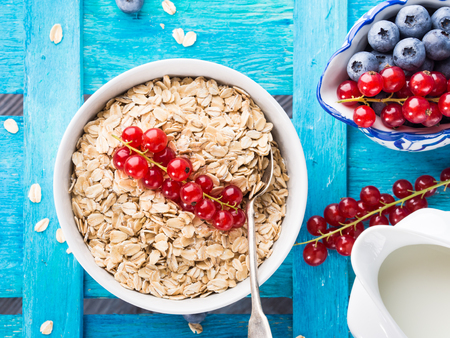 flatly: Bowl with oatmeal flakes with red currants for healthy breakfast on bright blue wooden background. Closeup