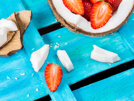 Half coconut with strawberries and coconut wedges and shreds on bright blue textured wooden background
