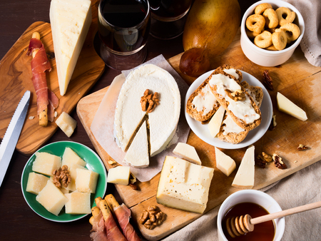 overhead view: Different types of cheese on wooden boards with wine, honey and walnuts. Overhead view Stock Photo