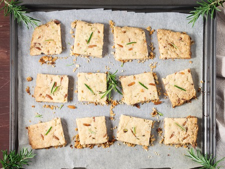 flatly: Freshly baked butter cookies with rosemary, pine nuts and pistachio on baking parchment, decorated with rosemary sprigs. Flat lay