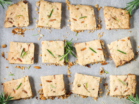 flatly: Freshly baked butter cookies with rosemary, pine nuts and pistachio on baking parchment, decorated with rosemary sprigs. Top view