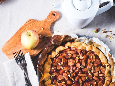flatly: Home made apple galette with cherry jam and pine and pistachio nuts on beige table cloth. Top view