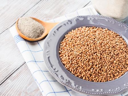 Buckwheat grain and flour on checkered napkin on wooden table