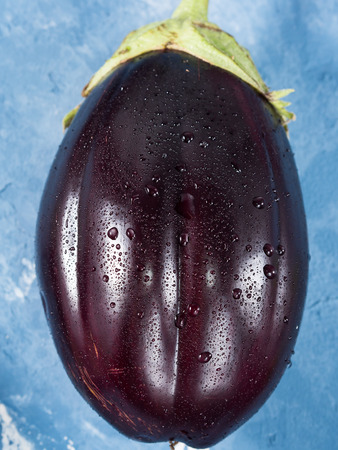 Purple eggplant with drops of water on textured background. Top view. Closeup Stock Photo
