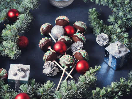 Blue spruce branches with christmas baubles and cake pops with colored sprinkles on green frosting on dark black concrete effect background. Copy space Stock Photo