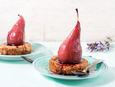 Mini tartelettes de polenta aux poires dans une sauce au vin rouge sur des assiettes pastel vertes avec des fleurs violettes sur fond pastel blanc et vert