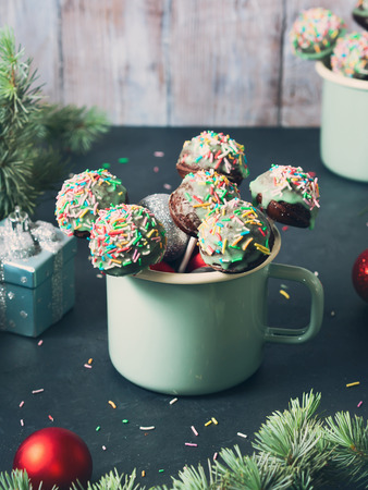 Bright christmas cake pops in green vintage enamel cups with green branches and baubles around on wooden background. Vertical toned image