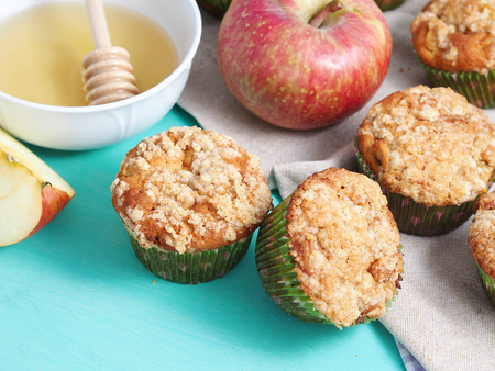 Apple crumb spiced muffins with streusel topping on green pastel wooden table with napkin and honey Stock Photo