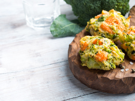 Baked vegetable patties with carrots, broccoli and cheese on dark wooden serving board. Copy space