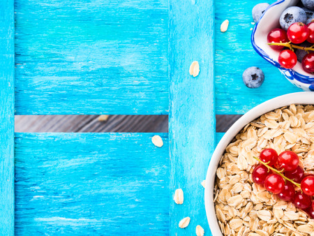 Vibrant blue wooden textured background with bowl of rolled oats and fresh berries