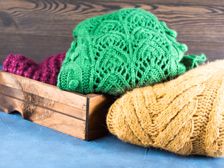 womans clothing: Winter womans woolen sweaters. Knitted girls clothing. Colorful pullovers on wooden background. Cozy clothes for the season.