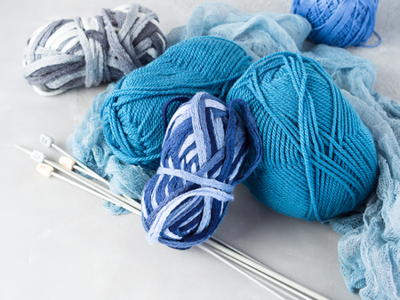 purl: Winter color wool yarn with knitting needles. Blue palette and gray clews. Stock Photo
