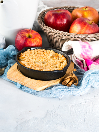 Home made apple crumble in cast iron skillet on wooden serving board. Cozy and healthy breakfast set with fruit. Vertical image