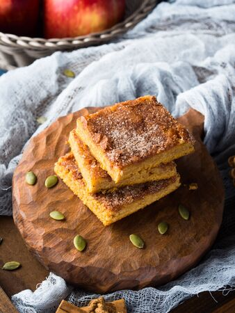 Stacked Christmas spiced pumpkin blondies topped with sugar and cinnamon. Baked square bar treat for winter breakfast. Sweet food still life on dark background. Vertical Stock Photo