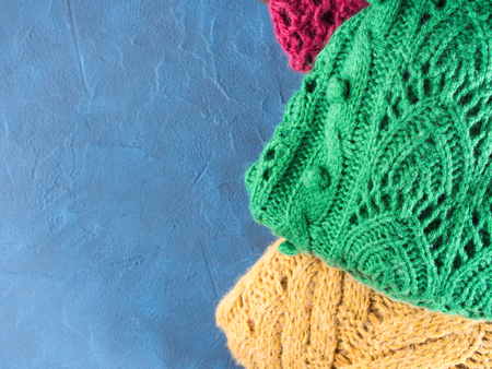 womans clothing: Winter womans woolen sweaters. Knitted girls clothing. Colorful pullovers on wooden background. Cozy clothes for the season. Copy space. Top view