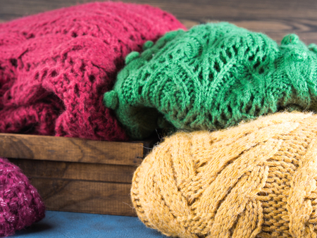pullovers: Winter womans woolen sweaters. Knitted girls clothing. Colorful pullovers on wooden background. Cozy clothes for the season.