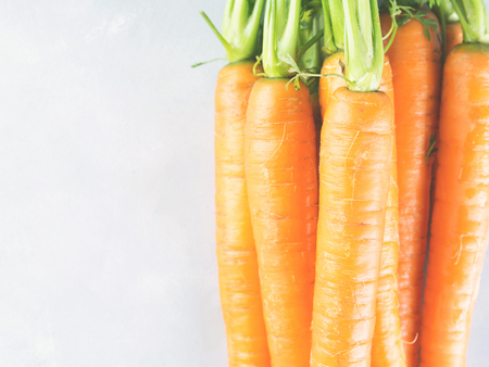 Fresh carrots on gray background. Healthy eating diet concept. Vegetables frame on table. Raw organic food. Toned