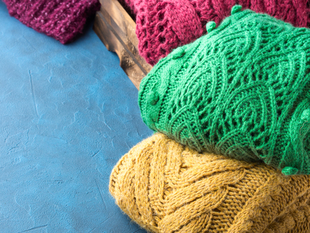 womans clothing: Winter womans woolen sweaters. Knitted girls clothing. Colorful pullovers on wooden background. Cozy clothes for the season. Copy space Stock Photo