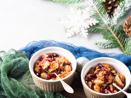 Christmas baked apple dessert with pomegranate seeds. Winter holidays treat on textured background